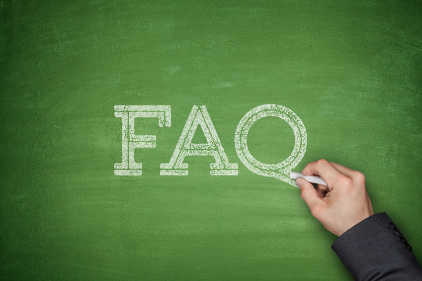 FAQ text concept on green blackboard with hand
